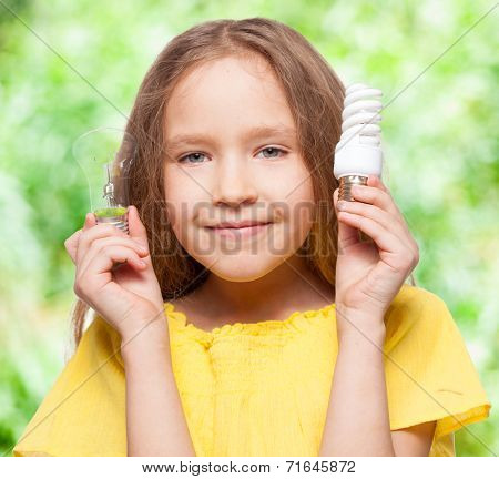 Child with bulbs. Girl holding an energy-saving and incandescent lamp