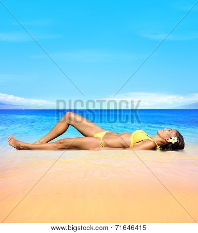 woman relaxing under sun in luxury spa retreat resort lying in sand.