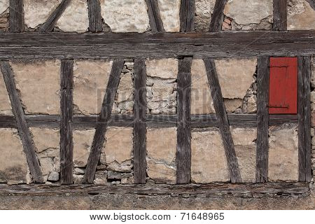 Truss of a ramshackle barn with a small red shutter