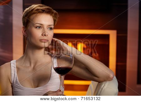 Daydreaming woman sitting in cosy room by fireplace, holding a glass of wine, daydreaming.