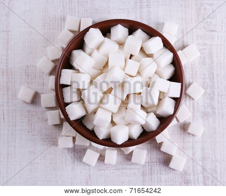 Refined sugar in color bowl on wooden background