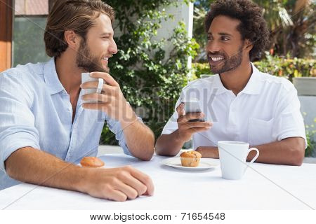 Two friends enjoying coffee together outside at the coffee shop