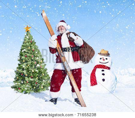 Santa claus holding sack and skis next to a christmas tree.
