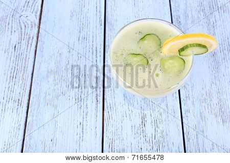 Cucumber cocktail with lemon on wooden background