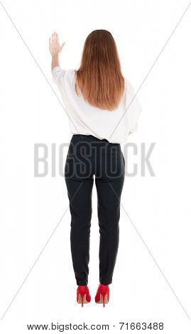 back view of business woman. Young woman in suit presses down on something. Isolated over white background. Rear view people collection. backside view of person. she holds his hand open, palm forward