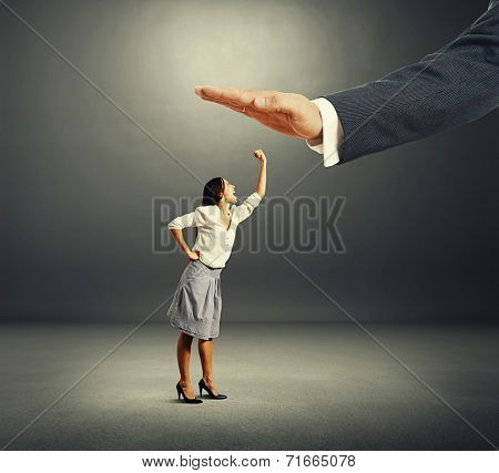 concept photo of conflict between subordinate and boss. screaming young businesswoman showing fist and looking up at big palm of her boss over dark background