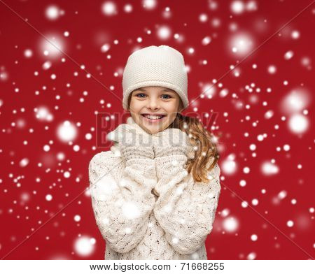 winter, happiness, christmas concept - smiling girl in white hat, muffler and glove