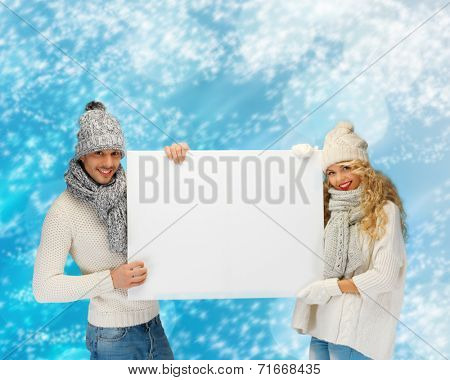 happiness, winter holidays, christmas, advertising and people concept - smiling couple in winter clothes holding big white blank board over blue snowy background