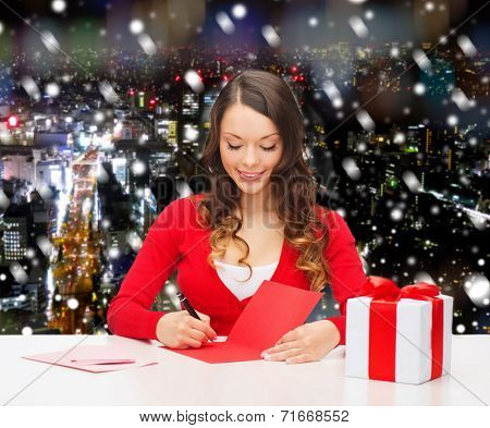 christmas, holidays, celebration, greeting and people concept - smiling woman with gift box writing letter or sending post card over snowy night city background