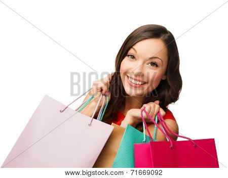 sale, gifts, christmas, x-mas concept - smiling woman in red dress with shopping bags