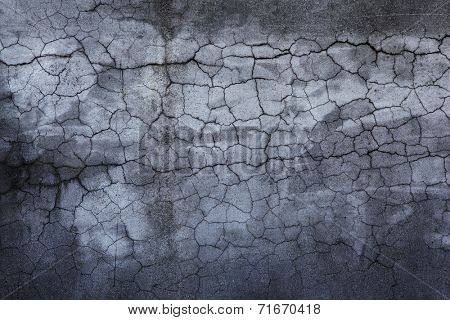 Darkish stone wall with many cracks.