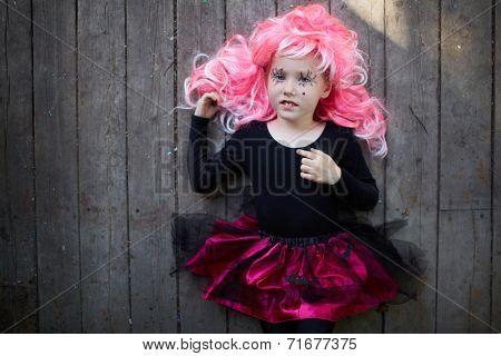 Portrait of happy Halloween girl in pink wig looking at camera