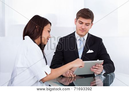 Doctor Showing Digital Tablet To Businessman