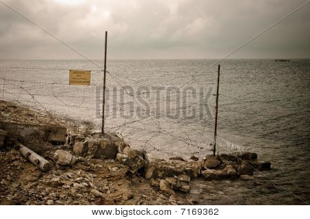 Fence Post With Barbed Wire On Coast