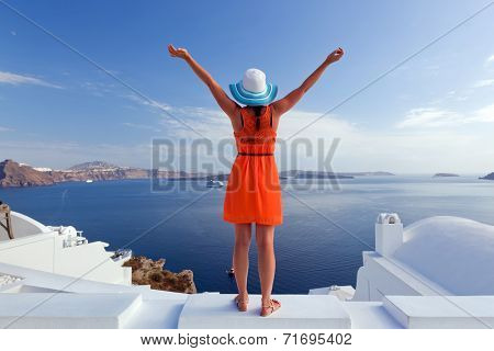 Happy woman in sun hat enjoying her holidays on Santorini island, Greece. View on Caldera and Aegean sea from Oia. Active, travel, tourist concepts