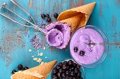 stock photo of gelato  - Tasty ice cream with fresh berries on old blue wooden table - JPG