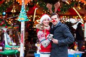 stock photo of merry-go-round  - Man and woman or  a couple  or friends during advent season or holiday in front of a carousel or  - JPG