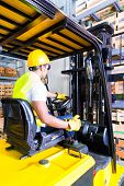 picture of lift truck  - Asian fork lift truck driver lifting pallet in storage warehouse - JPG