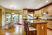 image of granite  - Light brown kitchen room with granite tops and kitchen island - JPG