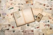 foto of nostalgic  - nostalgic vintage background with old handwritten postcards and open empty book - JPG