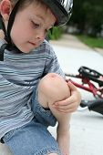 stock photo of scabs  - young boy examines his scraped knee after a bike accident - JPG