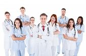 picture of medical staff  - Large diverse group of medical staff in white uniforms standing grouped behind a handsome middle-aged bearded doctor or physician isolated on white ** Note: Soft Focus at 100%, best at smaller sizes - JPG