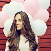 image of latex woman  - Happy young woman over red brick wall and holding pink and white balloons and gives a wink - JPG
