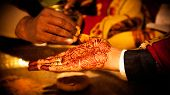 image of mehndi  - hand detail of indian groom with decorative mehndi and gold ring - JPG
