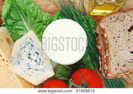 fresh aged french cheeses chops on big cutting board with tomatoes olive oil, rye bread and green chives isolated over white background