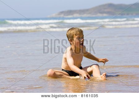 Young Boy Playing At The Edge Of The Ocean