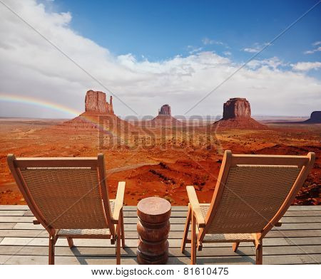 Red sandstone in the valley of the Navajo. Famous rock - mitts crosses the rainbow. Two chairs - deck chairs on the wooden platform are for tourists