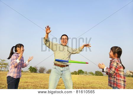 Happy Family Playing With Hula Hoops Outdoors