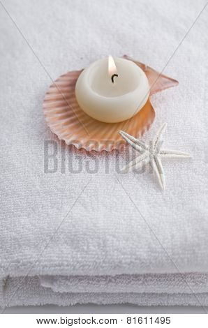 Lit-up candle with natural shells placed on white towel - spa still life