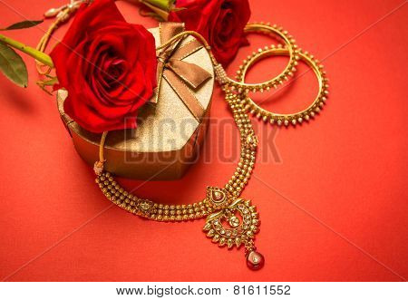 Traditional indian gold necklace and bangles set arranged with heart-shaped gift box and red rose flowers.