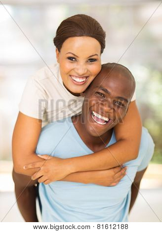 cheerful young african american couple having fun with piggyback