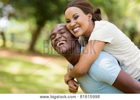 cheerful black woman enjoying piggyback ride on boyfriends back outdoors