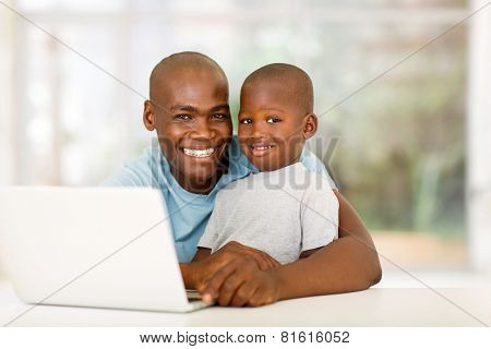handsome young african man relaxing at home with his little boy