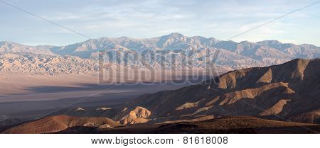 View on Death Valley in sunset light with dried lake and mountains on background