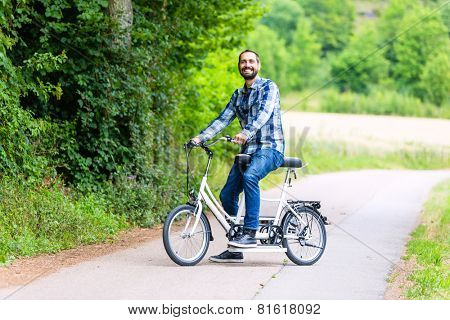 Man riding tandem bike on country lane