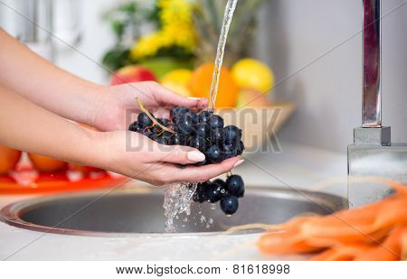 woman's hands washing a fresh grapes under the tap