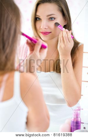 Beautiful girl looking in the mirror and applying cosmetic with brush, girl gets blush on the cheekbones. Powder, rouge