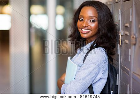 pretty female african student standing next to locker at college