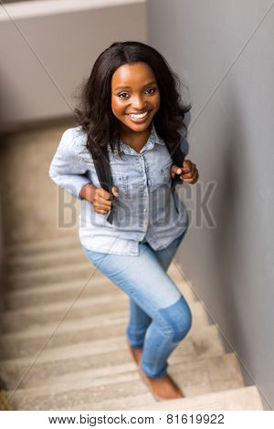 beautiful african college girl walking up the stairs on campus