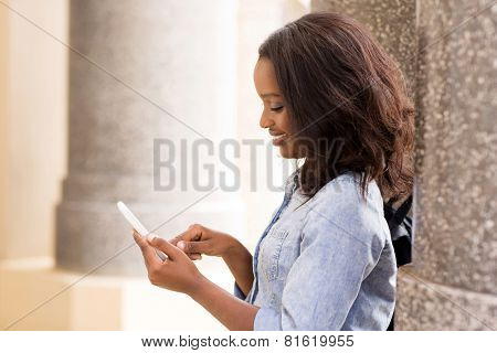 beautiful african university student texting on smart phone
