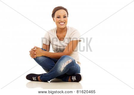cheerful afro american girl sitting on floor isolated on white