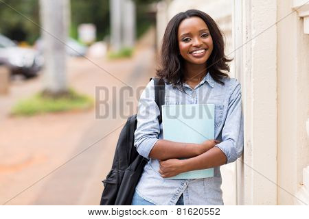 portrait of happy female african american college student holding a book