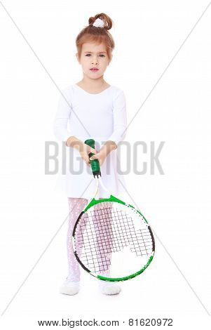 Little girl in sports dress holding a tennis racket.