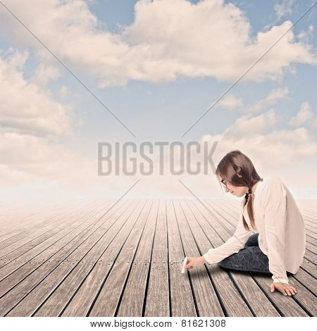 young girl drawing with chalk on a wharf