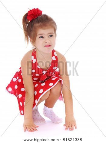 Adorable little girl squatted.