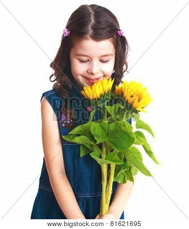 Adorable little girl is smelling flowers.